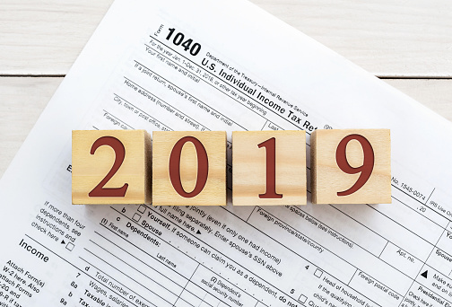 blocks reading 2019 with a blank 1040 tax form behind it