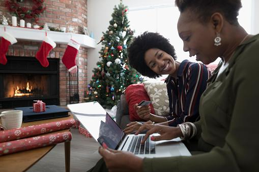 2 black women sitting by fireplace, looking at a laptop and smiling