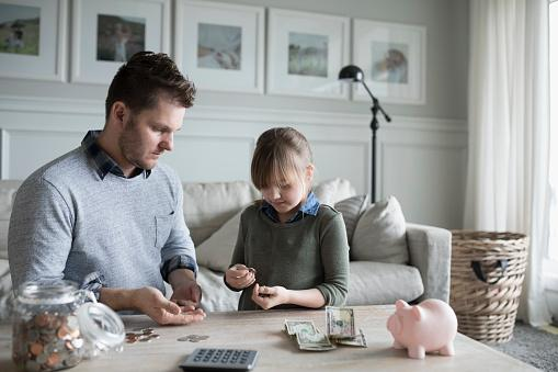 father sitting at table with daughter, counting money
