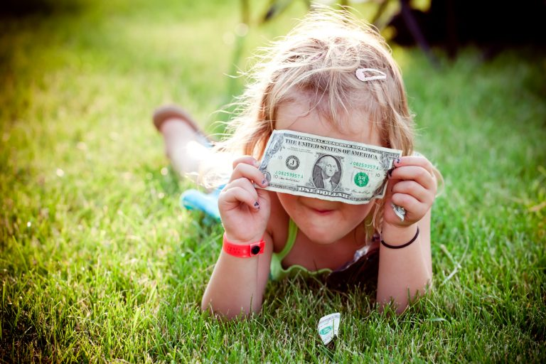 little blonde girl laying in the grass holding a dollar bill in front of her face