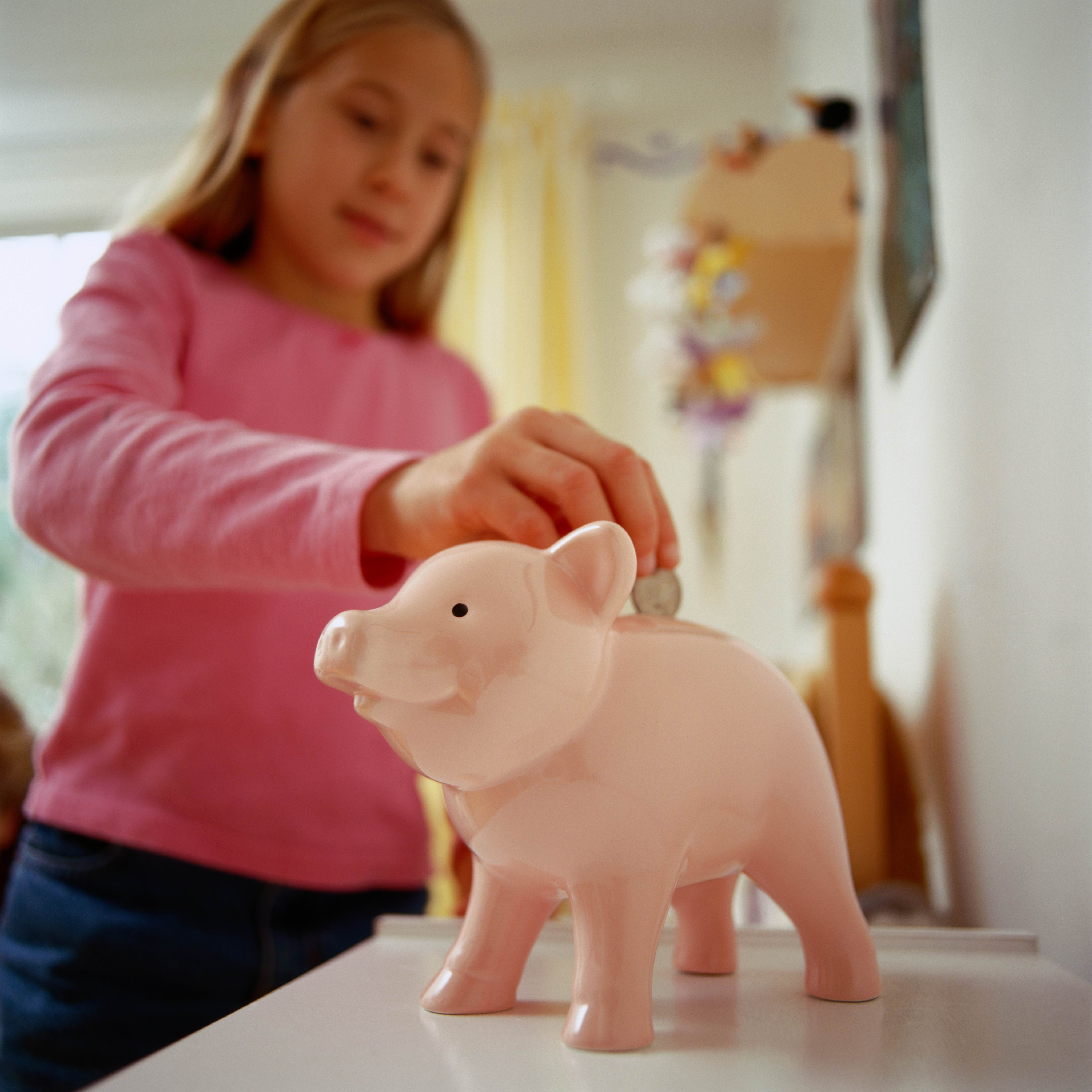 young girl putting a coin into a light pink piggy bank