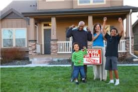 happy African american family standing in front of house with sold sign