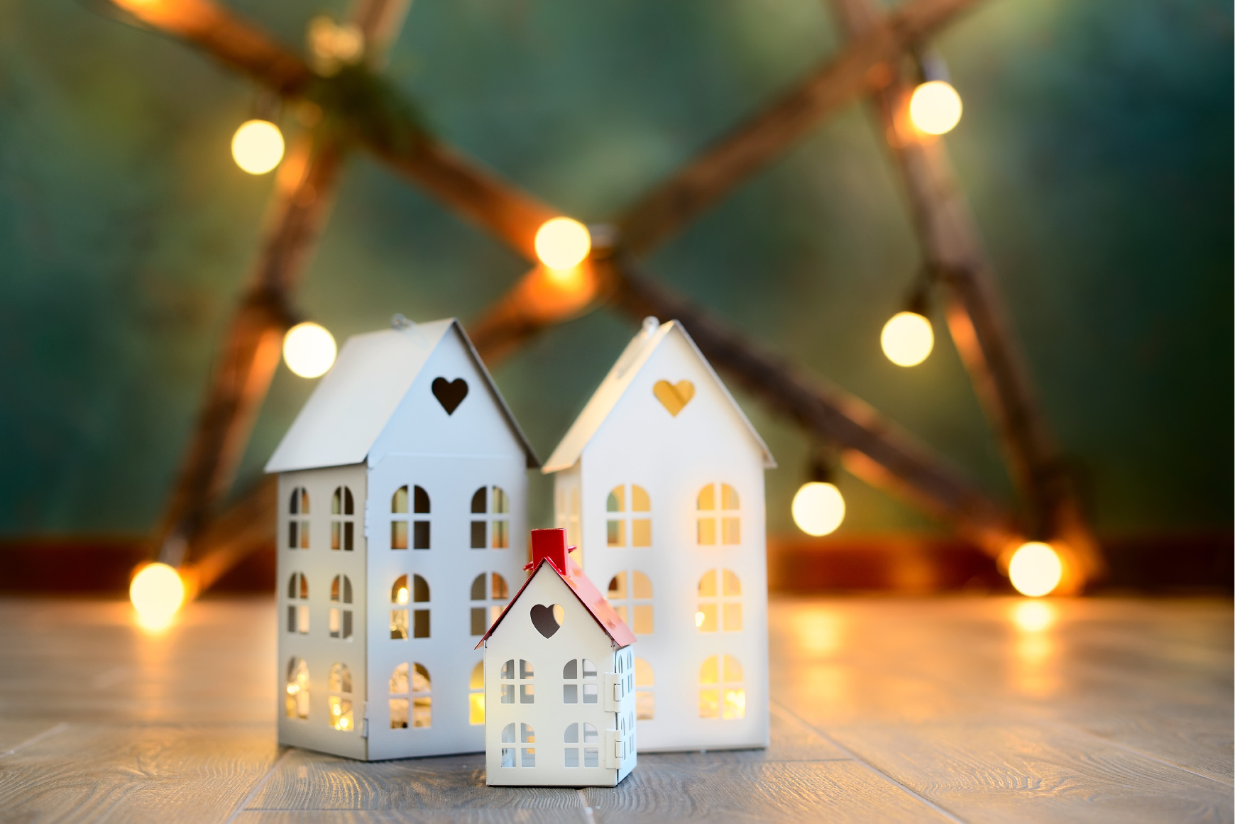 3 small white model houses with lighted star in background