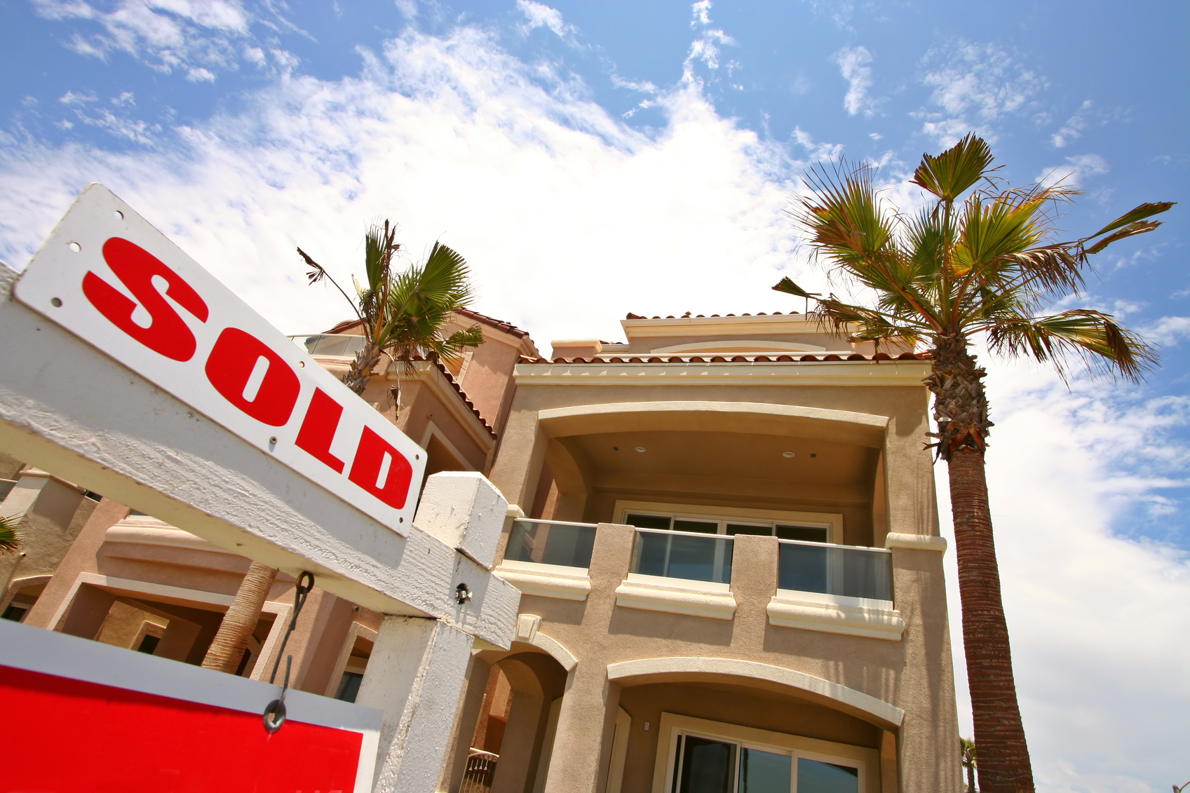 "two-story house with palm trees behind it and a white with red lettering ""sold"" sign in front"