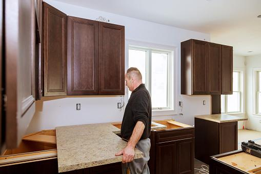 man holding new counter top in kitchen being remodeled
