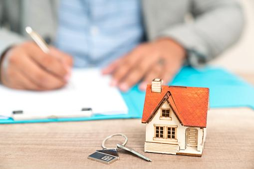 man's hand writing something in folder with tiny replica house and keys on desk