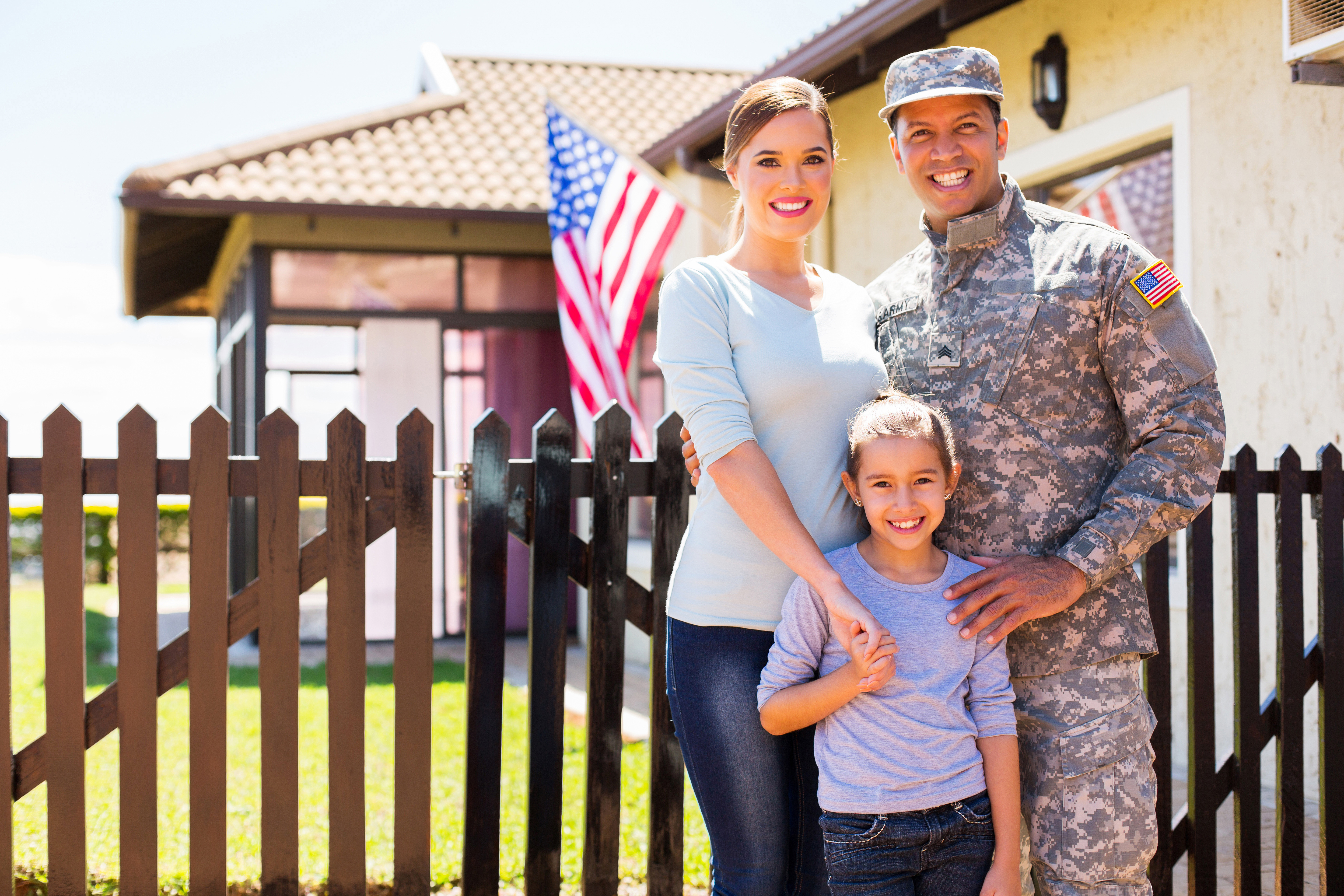 husband in military uniform with wife and daughter standing in front of house