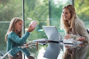 mother and young daughter sitting at table with laptop and piggy bank