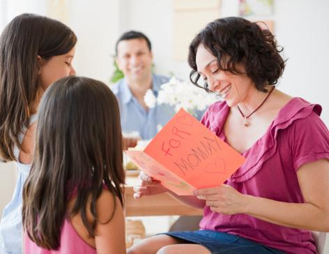 family sitting around table with mother reading card from daughters
