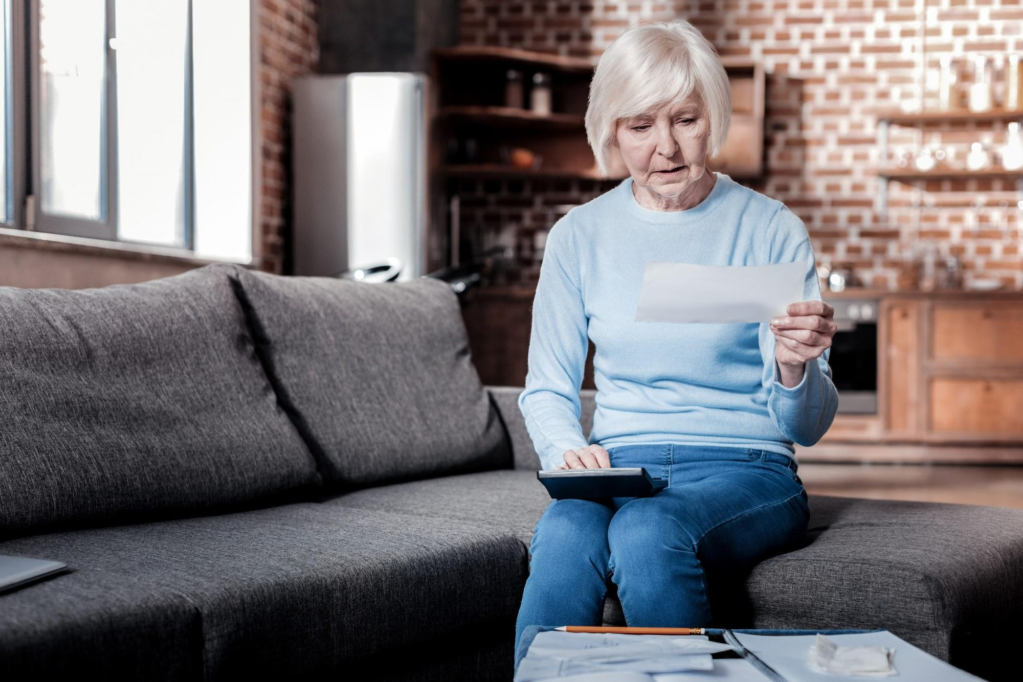older Caucasian woman sitting on couch in home looking at piece of paper
