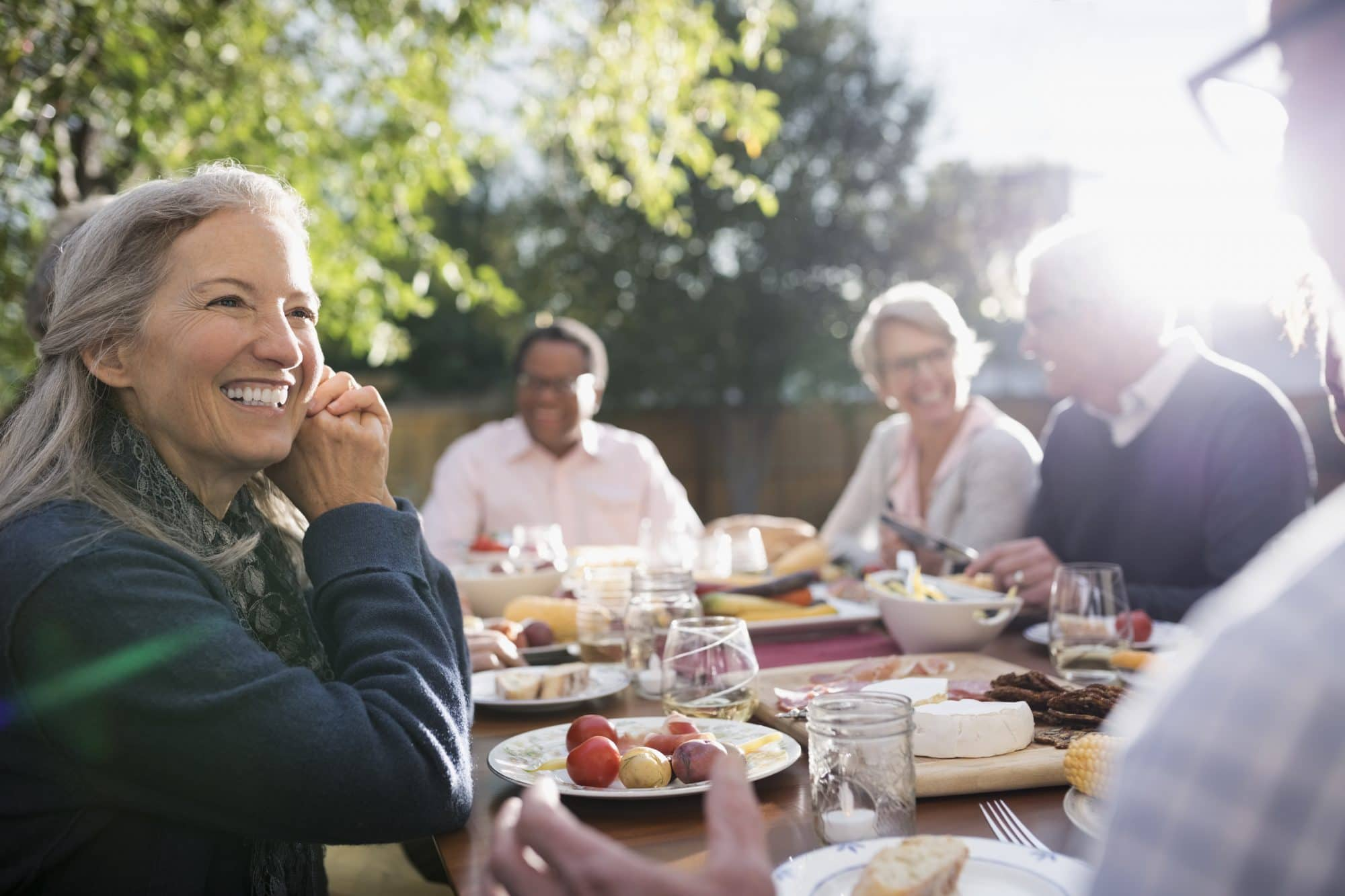 older people sitting around a table outside eating food and having a good time
