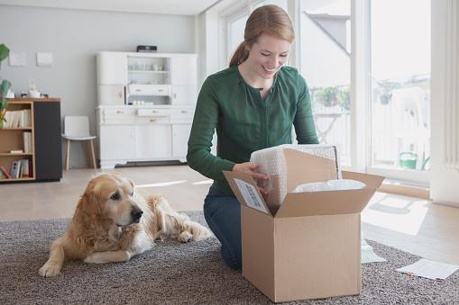smiling Caucasian woman opening delivery box at home with dog next to her