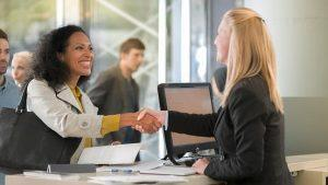 two smiling woman doing business and shaking hands