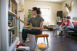 woman taking books off shelf and man using laptop in house
