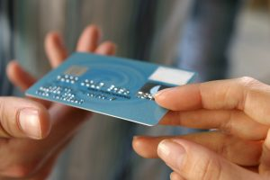 two hands holding blue debit card