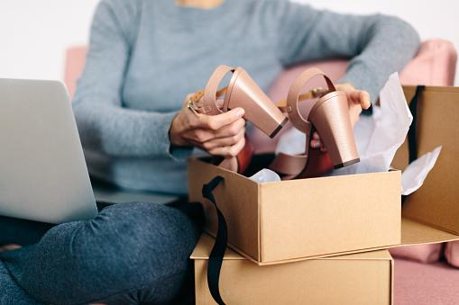 woman taking new shoes out of box with laptop on her lap, we can't see her face