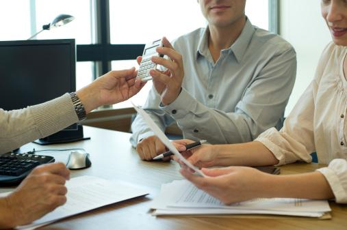 woman's hand handing calculator to couple across the desk from her