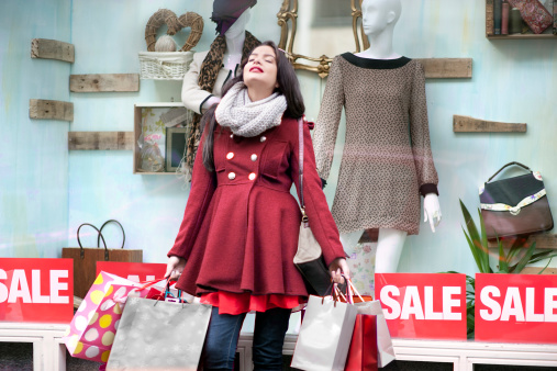 woman wearing winter coat holding multiple shopping bags in front of clothing store with SALE signs