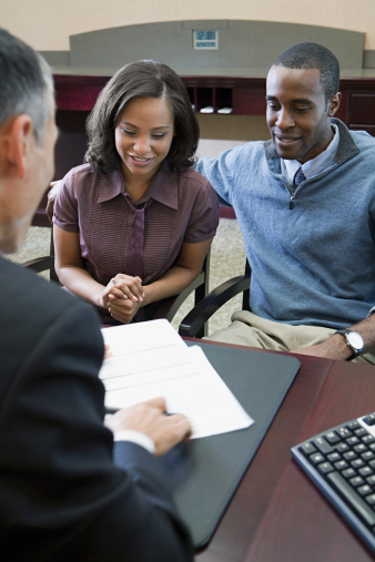 african american couple sitting at desk with financial advisor