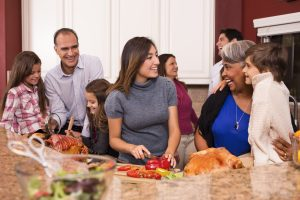 smiling family standing in kitchen with one woman chopping vegetables